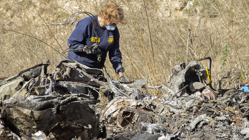An investigator, pictured here working at the scene of the helicopter crash that killed Kobe Bryant.