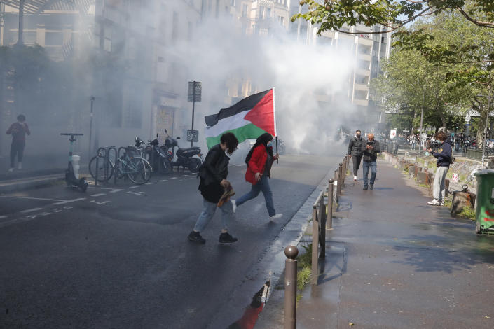 A demonstrator holding a Palesnian flag crosses a street during a banned protest in support of Palestinians in the Gaza Strip, Saturday, May, 15, 2021 in Paris. Marches in support of Palestinians in the Gaza Strip were being held Saturday in a dozen French cities, but the focus was on Paris, where riot police got ready as organizers said they would defy a ban on the protest. (AP Photo/Michel Euler)