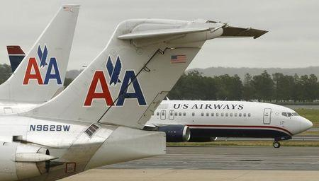 A US Airways plane passes American Airlines planes at Ronald Reagan National Airport in Washington