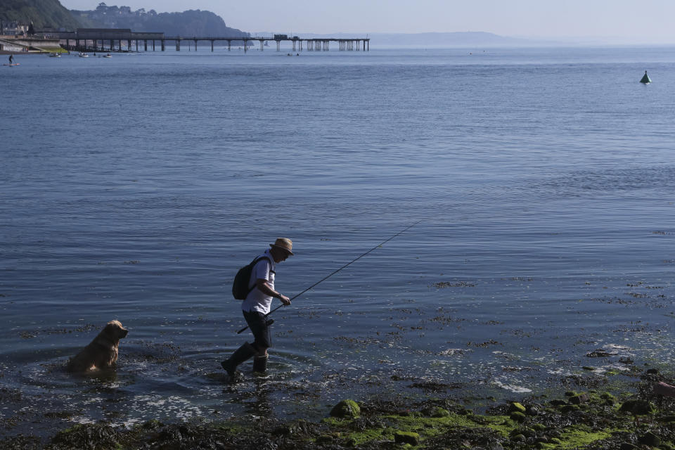 A man is followed by a dog as he moves to another spot to fish in the Teign estuary in Shaldon, Devon, England, Sunday July 18, 2021. (AP Photo/Tony Hicks)