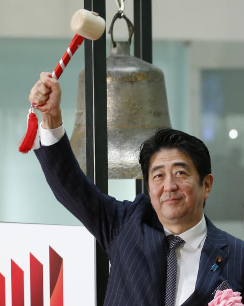 "Japanese Prime Minister Shinzo Abe poses for photographers after sounding a bell during a ceremony marking the last session of the year 2013 at the Tokyo Stock Exchange in Tokyo Monday, Dec. 30, 2013. ""Thanks to our efforts, the economy went from minus to positive,"" Abe said. With winter bonuses up by several hundred dollars on average, he said, ""You have to use that money, keep it moving."" Asian shares advanced Monday in light but upbeat pre-holiday trading, as Japan's Nikkei 225 index ended 2013 at its highest level in over six years. (AP Photo/Shizuo Kambayashi)"