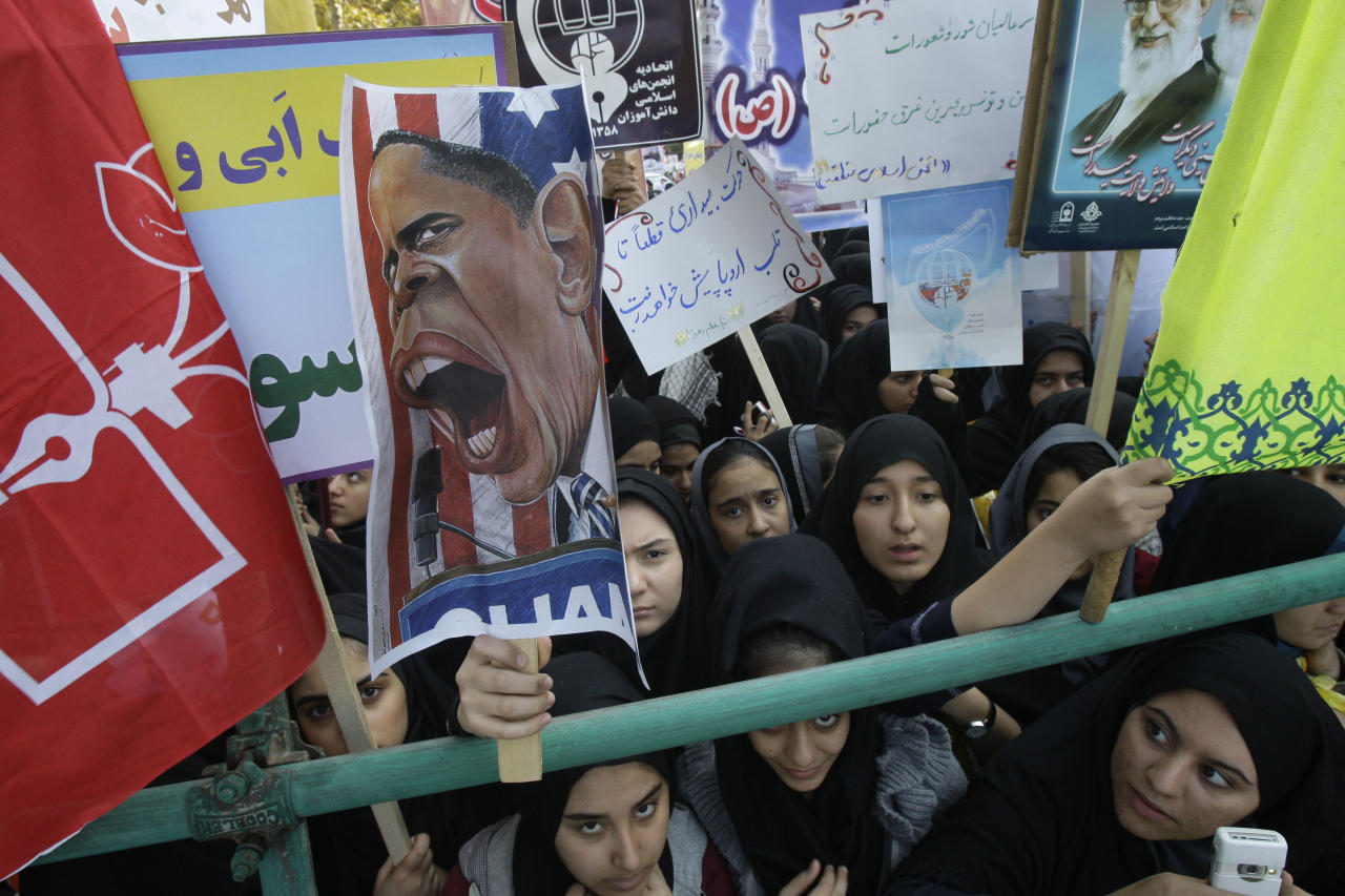 Iranian girls, one of them holding up a caricature of President Barack Obama while others hold pro-government posters, attend an annual state-backed rally in front of the former U.S. Embassy in Tehran, Iran, Friday, Nov. 2, 2012. The rally marks the Nov. 4, 1979, storming of the building by militant students who held 52 Americans hostage for 444 days to protest U.S. failure to hand over the toppled shah Mohammad Reza Pahlavi to Iran for trial. Gen. Mohammad Reza Naqdi of the powerful Revolutionary Guard, not shown, addressed the rally saying the U.S. must annul the CIA, pull out its warships from the Persian Gulf and dismantle its military bases from 50 countries around the world if it wants to restore ties with Tehran. (AP Photo/Vahid Salemi)