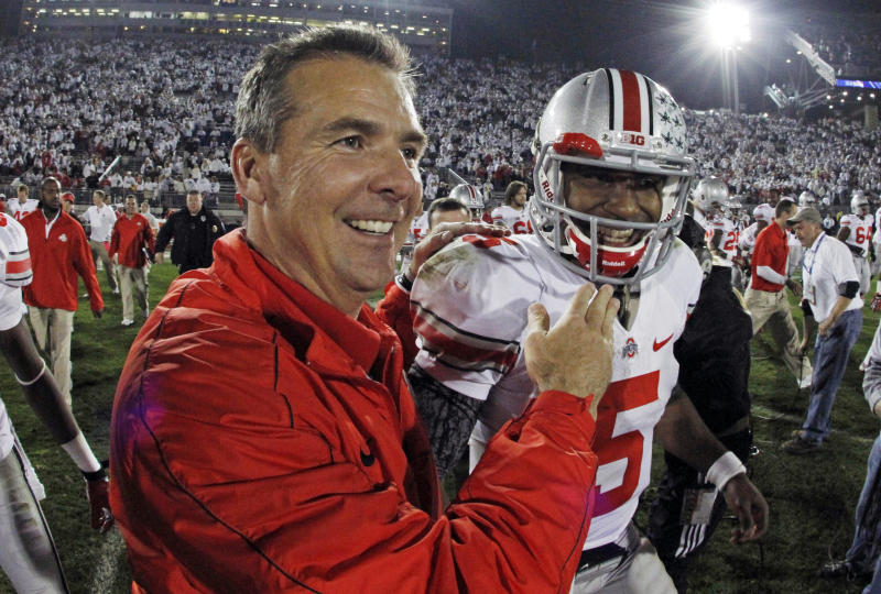 In this photo made using a fisheye lens, Ohio State head coach Urban Meyer, left, celebrates with Ohio State quarterback Braxton Miller (5) at the end of a 35-23 win over Penn State in an NCAA college football game in State College, Pa., Saturday, Oct. 27, 2012. (AP Photo/Gene J. Puskar)