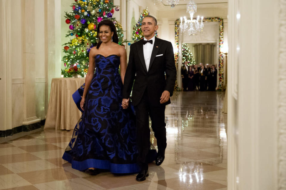 <p>Now that's how you make a grand entrance! The first lady arrived hand-in-hand with her husband to the 2015 Kennedy Center Honors reception in the East Room of the White House in a strapless cobalt blue and black gown. The dress featured a sheer overlay with a floral design and a curlicue train. She kept her hair down, combed back, and straight, and wore large gold earrings. <i>Photo: AP</i></p>