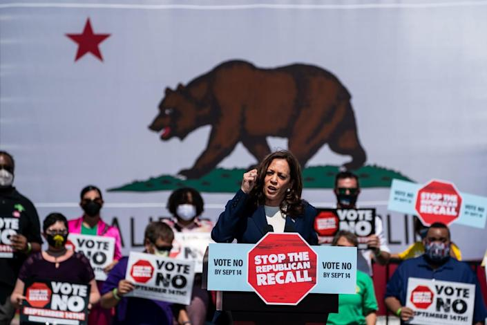 Kamala Harris speaks to the crowd. Behind her is a huge California flag and people holding up anti-recall placards.