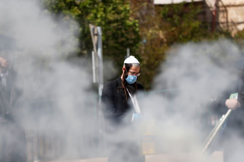An Ultra-Orthodox Jewish man wears a face mask for protection related to the coronavirus as he burns leaven in the Mea Shearim neighbourhood of Jerusalem ahead of the Jewish holiday of Passover
