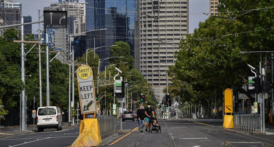 Two people cross a Melbourne street with face masks, pushing a pram with a child in it.