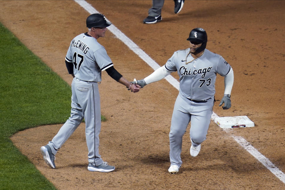 Chicago White Sox's Yermin Mercedes, right, is congratulated by third base coach Joe McEwing after his home run off Minnesota Twins' Willians Astudillo in the ninth inning of a baseball game, Monday, May 17, 2021, in Minneapolis. (AP Photo/Jim Mone)