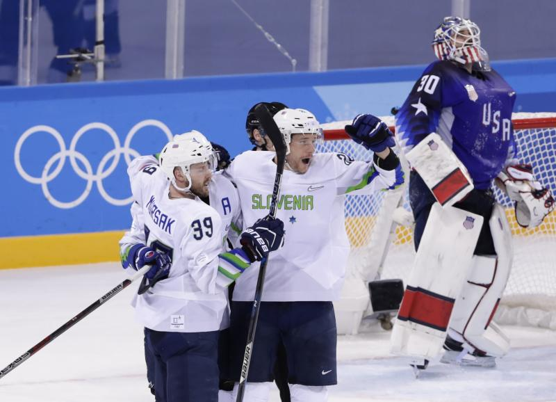 Jan Urbas (26), of Slovenia, celebrates with teammate Jan Mursak (39), as goaltender Ryan Zapolski (30), reacts after Mursak scored the game winning goal during the overtime period of the preliminary round of the men's hockey game at the 2018 Winter Olympics in Gangneung, South Korea, Wednesday, Feb. 14, 2018. Slovenia won 3-2. (AP Photo/Frank Franklin II)