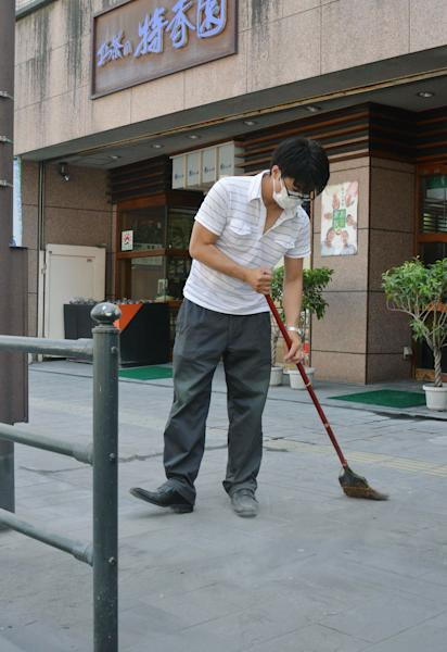 A store worker wearing a mask sweeps the pavement covered by ash Monday morning, Aug. 19, 2013 after the Sakurajima volcano erupted Sunday afternoon in Kagoshima, on the southern Japanese main island of Kyushu. People in the city wore masks and raincoats and used umbrellas to shield themselves from the ash after the eruption. (AP Photo/Kyodo News) JAPAN OUT, MANDATORY CREDIT