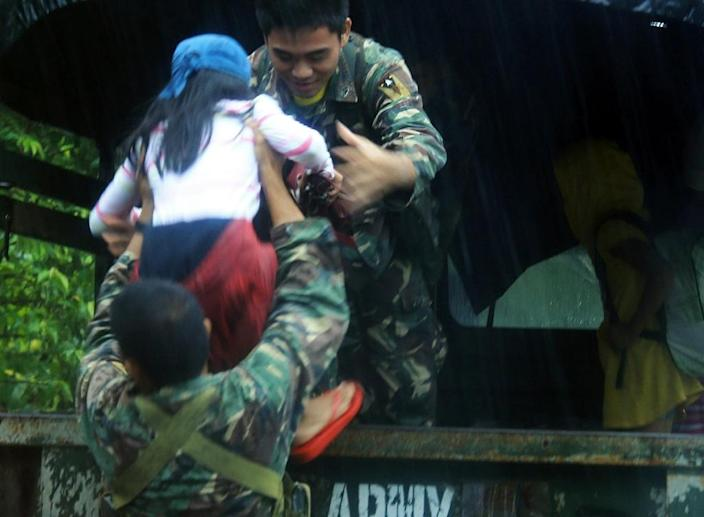 Military personnel evacuate residents from a village south of Manila on December 14, 2015 (AFP Photo/Charism Sayat )