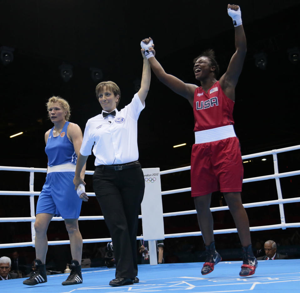 The United States' Claressa Shields, in red, celebrates winnning against Russia's Nadezda Torlopova, in blue, in their women's middleweight 75-kg boxing gold medal match at the 2012 Summer Olympics, Thursday, Aug. 9, 2012, in London. (AP Photo/Ivan Sekretarev)