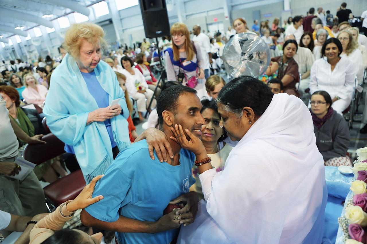 """Mata Amritanandamayi, also known as """"The Hugging Saint"""" embraces followers on July 10, 2012 in New York City. The Hindu spiritual leader and guru is on a 10-city U.S. tour, where she is expected to bless thousands of people individually at free public """"darshan"""" gatherings. Amritanandamayi, 58, from India's southern state of Kerala, is considered a living saint by her followers, who refer to her as """"Amma"""" or mother. She has been giving the public """"darshan"""" gatherings for 35 years, with the aim of bringing good fortune, well-being and grace to her followers through her embrace. Participants are encouraged to donate to her global charitable organizations, known collectively as """"Embracing the World.""""  (Photo by John Moore/Getty Images)"""
