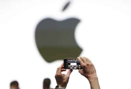 An audience member takes a photo of the Apple logo before the start of the company's annual developer conference in San Jose