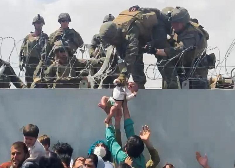 A baby is handed over to the American army over the perimeter wall of the airport for it to be evacuated, in Kabul, Afghanistan