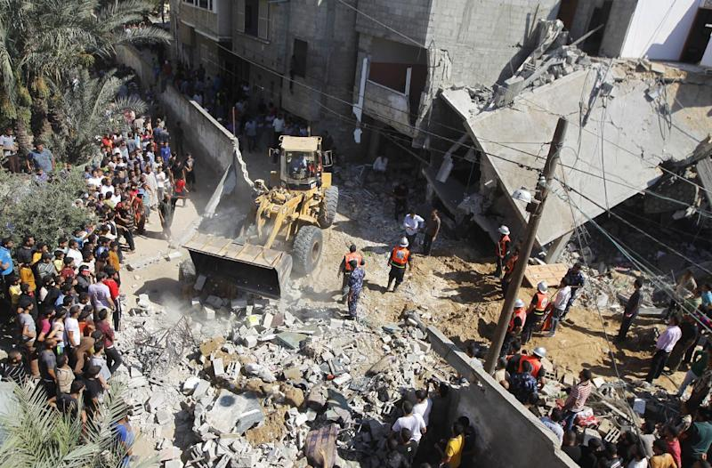 Palestinian rescue workers use a bulldozer to remove debris following an Israeli air strike in the southern Gaza town of Khan Yunis, on July 8, 2014 (AFP Photo/Said Khatib)