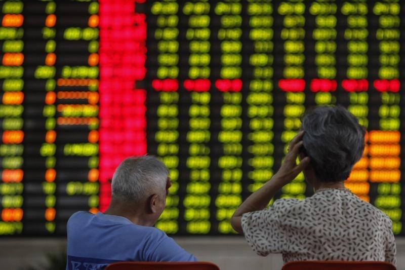 Investors sit in front of an electronic board showing stock information at a brokerage house in Shanghai