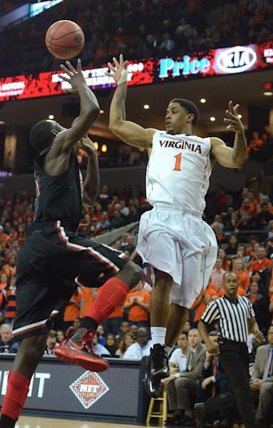 Virginia's Jontel Evans feeds the ball to teammate Justin Anderson over St. John's Sir'Dominic Pointer during an NIT college basketball game in Charlottesville, Va.., Sunday, March 24, 2013. Virginia won 68-50. (AP Photo/Pat Jarrett)