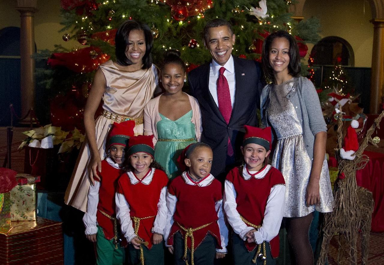 The first family, from left, first lady Michelle Obama, Sasha Obama, President Barack Obama and Malia Obama, pose with children dressed like elves at the National Building Museum in Washington, Sunday, Dec. 9, 2012. The first family is attending the taping of the 2012 Christmas in Washington. (AP Photo/Manuel Balce Ceneta)