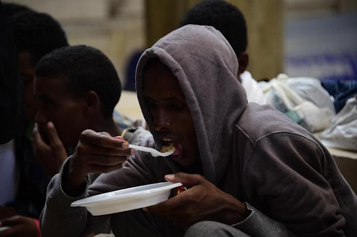 Migrants from Eritrea eat a meal they received from aid workers at the Milan train station on June 11, 2015 (AFP Photo/Olivier Morin)
