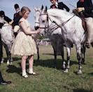 <p>An 11-year-old Princess Anne greets a friendly animal at the Windsor Horse Show. Like her mother, Anne would become an avid equestrian—and later, even compete at the Olympics in the sport.</p>
