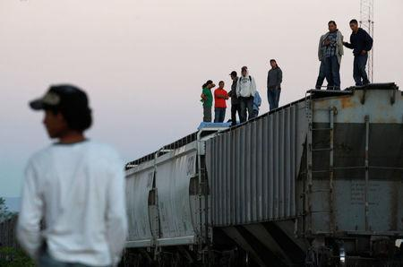 """Central American migrants stand atop wagons while waiting for the freight train """"La Bestia"""", or the Beast, to travel to north Mexico to reach and cross the U.S. border, in Arriaga in the state of Chiapas January 10, 2012. REUTERS/Jorge Luis Plata/File Photo"""