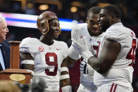 """Alabama quarterback Bryce Young (9) wears the leather helmet from the """"Old Leather Helmet Trophy"""" as he, Evan Neal (73) and Phidarian Mathis (48) celebrate their win over Miami in the Chick-fil-A Kickoff NCAA college football game Saturday, Sept. 4, 2021, in Atlanta. (AP Photo/John Bazemore)"""