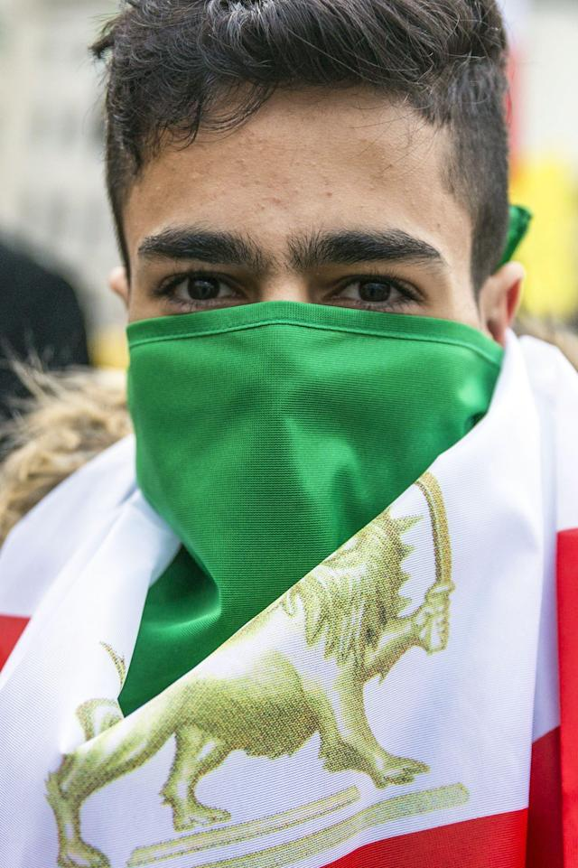 <p>A protester covers his face with the flag of the Iranian consitutional monarchy era as he attends a protest near Brandenburg Gate in Berlin, Germany, Jan. 6, 2018. (Photo: OMER MESSINGER/EPA-EFE/REX/Shutterstock) </p>