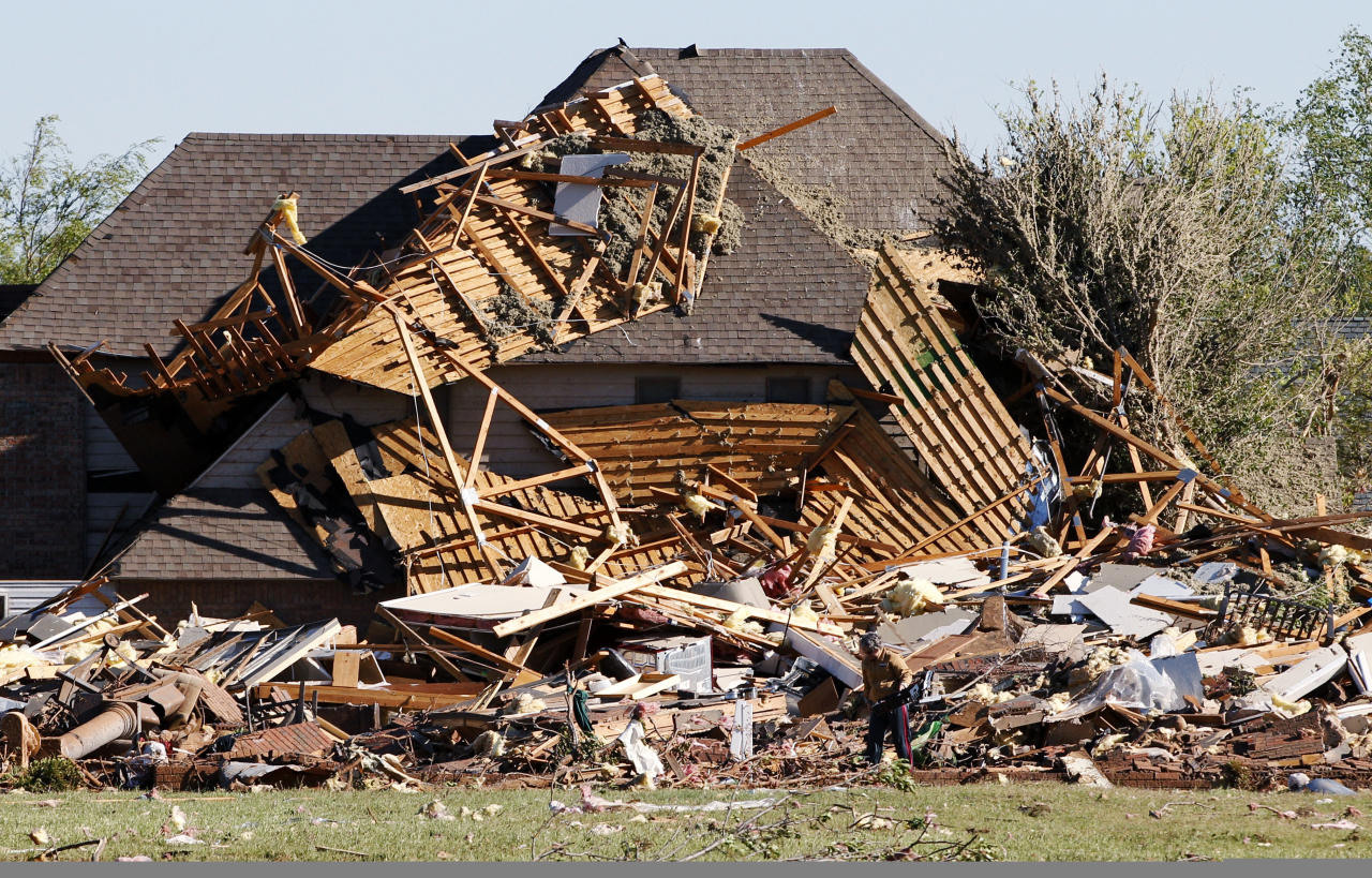 Sue Lord is dwarfed by the debris from her home, which is piled up on the neighbor's home, following a tornado in Woodward, Okla., Sunday, April 15, 2012. Lord was in the home when the tornado struck, but was not injured. (AP Photo/Sue Ogrocki)