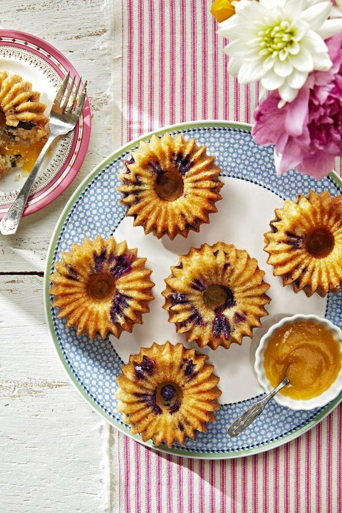 """<p>Mom will love these bite-sized bundt cakes that she can cover with as much sweet lemon curd as she pleases.</p><p><strong><a href=""""https://www.countryliving.com/food-drinks/a27245094/meyer-lemon-blueberry-cake-recipe/"""" rel=""""nofollow noopener"""" target=""""_blank"""" data-ylk=""""slk:Get the recipe"""" class=""""link rapid-noclick-resp"""">Get the recipe</a>.</strong></p><p><strong><a class=""""link rapid-noclick-resp"""" href=""""https://www.amazon.com/Wilton-2105-445-Excelle-6-Cavity-Fluted/dp/B0000DIX7S/?tag=syn-yahoo-20&ascsubtag=%5Bartid%7C10050.g.3185%5Bsrc%7Cyahoo-us"""" rel=""""nofollow noopener"""" target=""""_blank"""" data-ylk=""""slk:SHOP MINI BUNDT CAKE PANS"""">SHOP MINI BUNDT CAKE PANS</a><br></strong></p>"""