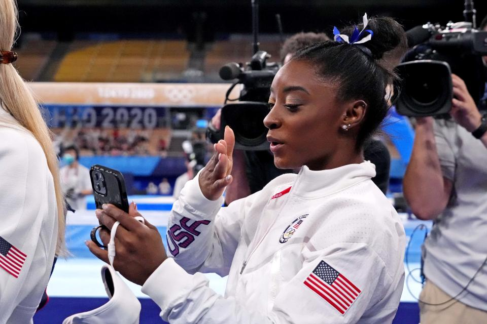 Aug 3, 2021; Tokyo, Japan; Simone Biles (USA) talks on a phone after competing on the balance beam during the Tokyo 2020 Olympic Summer Games at Ariake Gymnastics Centre. Mandatory Credit: Robert Deutsch-USA TODAY Sports