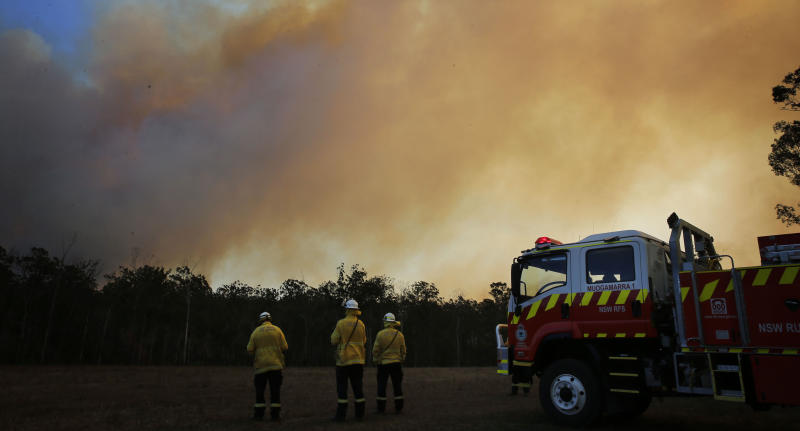 NSW firefighters are seen here at a property at Old Bar as a bushfire burns. A state of emergency has been declared.