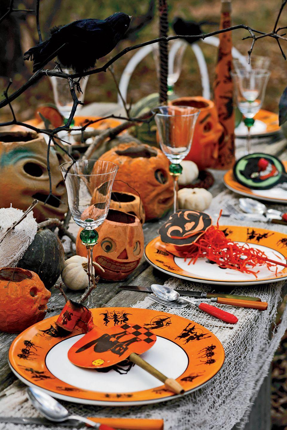 <p>A faux feathered bird, like a black crow, is the perfect addition to a Halloween table. Set a few on top of black spray-painted tree branches to achieve a realistic feel. Don't forget to complete the look with everything from creepy pumpkin designs to a white gauze tablecloth.</p>