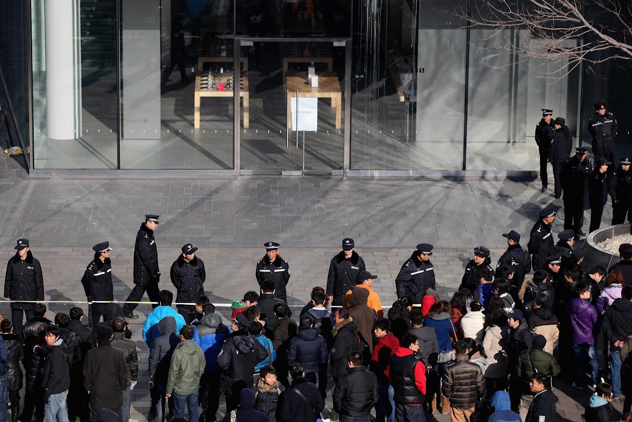 BEIJING, CHINA - JANUARY 13:  Police officers seal off the area near Apple's Beijing flagship store on January 13, 2012 in Beijing, China. Chinese angry crowd shouted and threw eggs outside Apple's Beijing flagship store after it failed to open on schedule Friday to sell iPhone 4S.  (Photo by Feng Li/Getty Images)