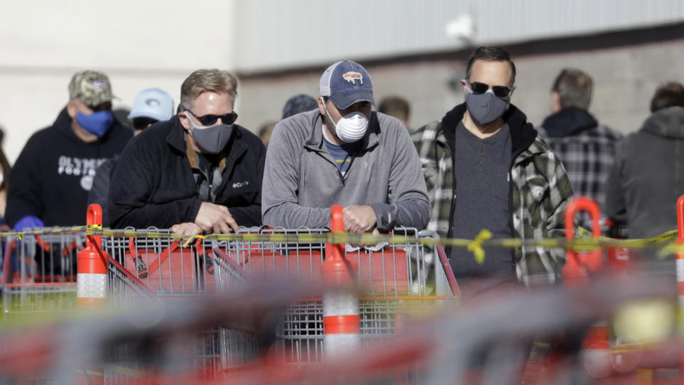 People wear masks as they wait in line at Costco Saturday, April 4, 2020, in Salt Lake City. The Centers for Disease Control and Prevention is now advising Americans to voluntarily wear a basic cloth or fabric face mask to help curb the spread of the new coronavirus. (AP Photo/Rick Bowmer)