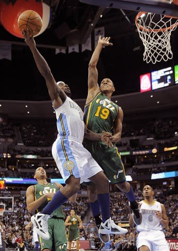 Denver Nuggets guard Ty Lawson (3) goes up for a shot against Utah Jazz shooting guard Raja Bell (19) during the second quarter of an NBA basketball game, Sunday, Jan. 15, 2012, in Denver. (AP Photo/Jack Dempsey)