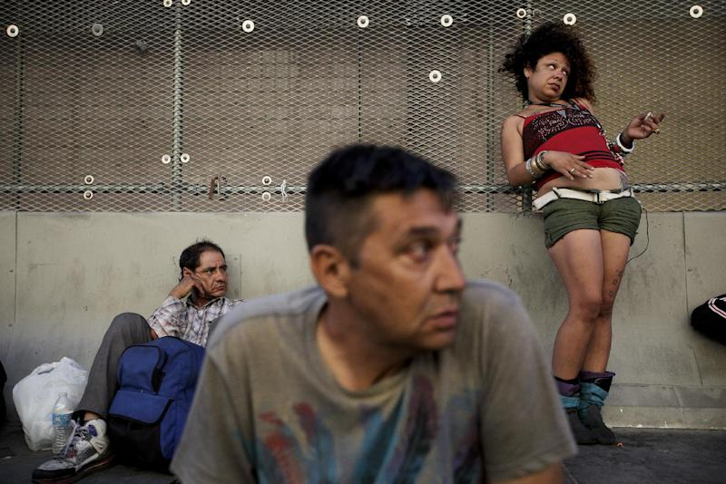 George Mendez, foreground, a 55-year-old recovering alcoholic, sits in front of a drunk woman in the Skid Row area of Los Angeles on Tuesday, July 23, 2013. The area, originally agricultural until the 1870s when railroads first entered Los Angeles, has maintained a transient nature through the years from the influxes of short-term workers, migrants fleeing economic hardship during the Great Depression, military personnel during World War II and the Vietnam conflict, and low-skilled workers with limited transportation options who need to remain close to the city's core, according to the Los Angeles Chamber of Commerce. (AP Photo/Jae C. Hong)