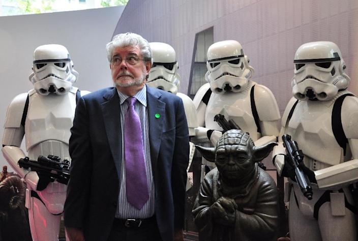 Filmmaking legend George Lucas of Disney's Lucasfilms poses with characters from the Star Wars films at the opening of Disney's Lucasfilms' new animation production facility, the Sandcrawler in Singapore, January 16, 2014 (AFP Photo/Stefanus Ian)