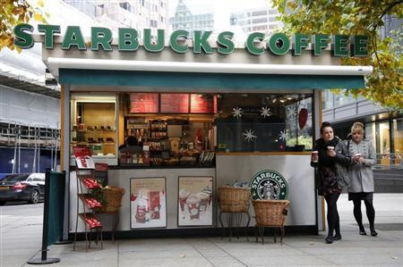 Customers leave a Starbucks coffee kiosk in the financial district of the City of London
