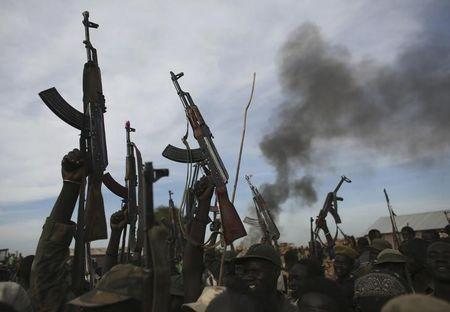 Rebel fighters hold up their rifles as they walk in front of a bushfire in a rebel controlled territory in Upper Nile State