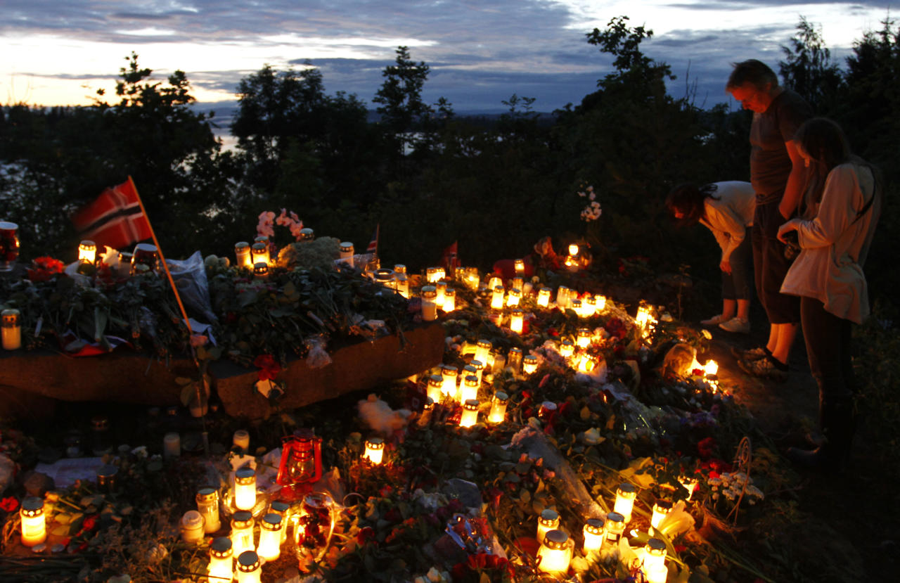 People read letters placed between flowers and candles in Utvica near Sundvollen close to the Utoya island, near Oslo, Norway, Tuesday, July 26, 2011, in memory of the eight people killed in Friday's blast in Oslo and the 68 who died in the shooting at the youth camp on Utoya. (AP Photo/Ferdinand Ostrop)