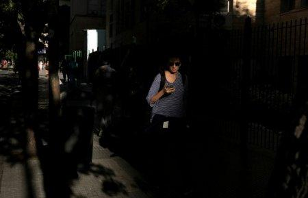 A woman uses her mobile phone as she walks on a street in Buenos Aires, Argentina, March 15, 2018. Picture taken March 15, 2018. REUTERS/Marcos Brindicci