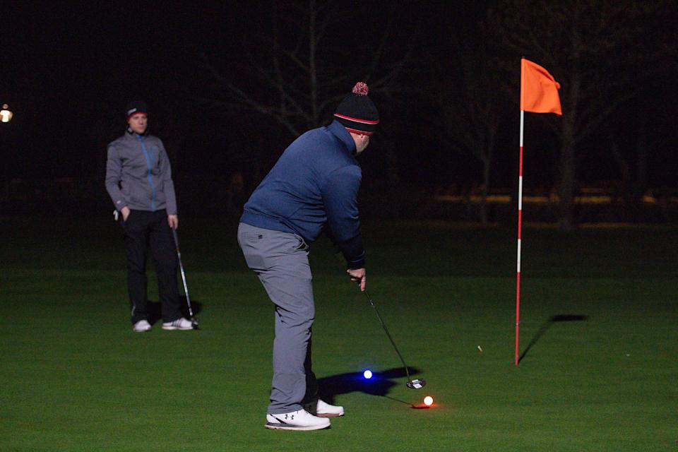Golfers use neon coloured balls whilst under floodlights at Morley Hayes Golf centre in Ilkeston, Derbyshire. The club is believed to be the first to reopen, with the first tee times at 0001, following the easing of England's lockdown restrictions to allow greater freedom outdoors. Picture date: Monday March 29, 2021.
