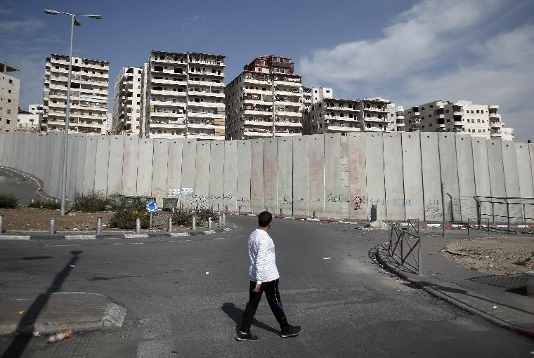 A Palestinian walks past Israel's controversial separation barrier surrounding buildings of the Shuafat refugee camp in East Jerusalem, on November 14, 2014 (AFP Photo/Thomas Coex)