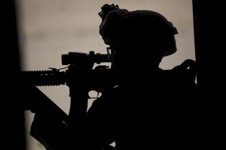 A U.S. Marine aims his weapon during a non-live fire MOUT training at US Marine Corps: Marines Air Ground Combat Center in Twentynine Palms