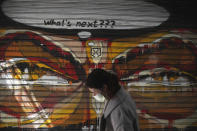 A woman wearing a face mask to protect against coronavirus, passes in front of graffiti painted on the shutter of a closed restaurant during a lockdown order by the Greek government to control the spread of the virus, in Athens, Monday, March 30, 2020. Greece's prime minister is calling on all his cabinet ministers and the lawmakers of his center-right New Democracy party to donate 50% of their salaries over the next two months to the fight against the spread of the new coronavirus. (AP Photo/Thanassis Stavrakis)