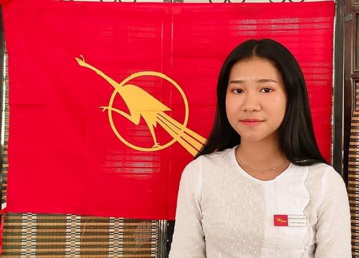 An undated photo shows Hnin, a Myanmar teacher, posing in front of National League for Democracy party flag in Hpakant Township