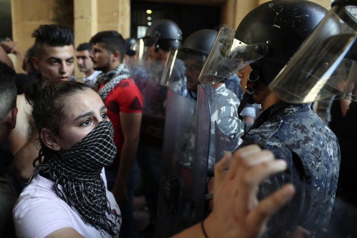 FILE - In this June 6, 2021, file photo, riot police stand guard during a demonstration against the political leadership the protesters blame for the economic and financial crisis, in front of the Ministry of Economy, in downtown Beirut, Lebanon. Lebanon's local currency hit a new record low on Sunday, June 13, 2021, with the country's economic and political crisis worsening with no apparent solutions in the near future. (AP Photo/Bilal Hussein, File)