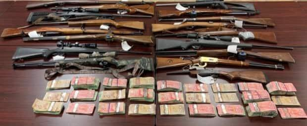 Seventeen long guns and an undisclosed amount of cash were found inside a Tobique First Nation residence last week. (RCMP New Brunswick - image credit)