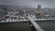 An aerial view of the Morrison Bridge and downtown Portland, Ore., is seen during a snowstorm, on Friday, Feb. 12, 2021. A winter storm has blanketed the Pacific Northwest with ice and snow, leaving hundreds of thousands of people without power and disrupting travel across the region. (Brooke Herbert/The Oregonian via AP)